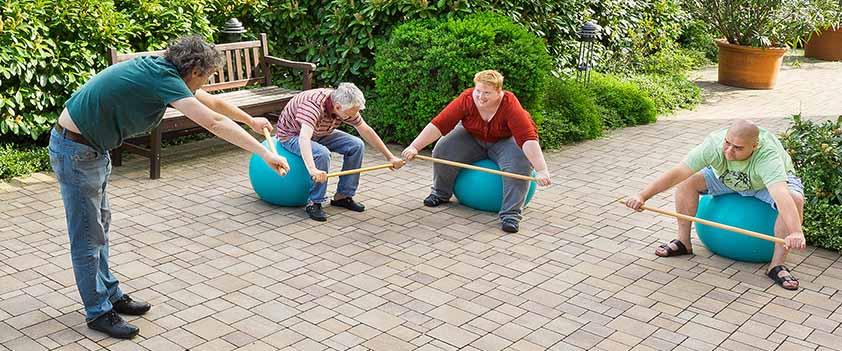 Patienten trainieren auf Gymnastikbällen im Garten des MEDIAN Haus Talblick Bad Dürkheim
