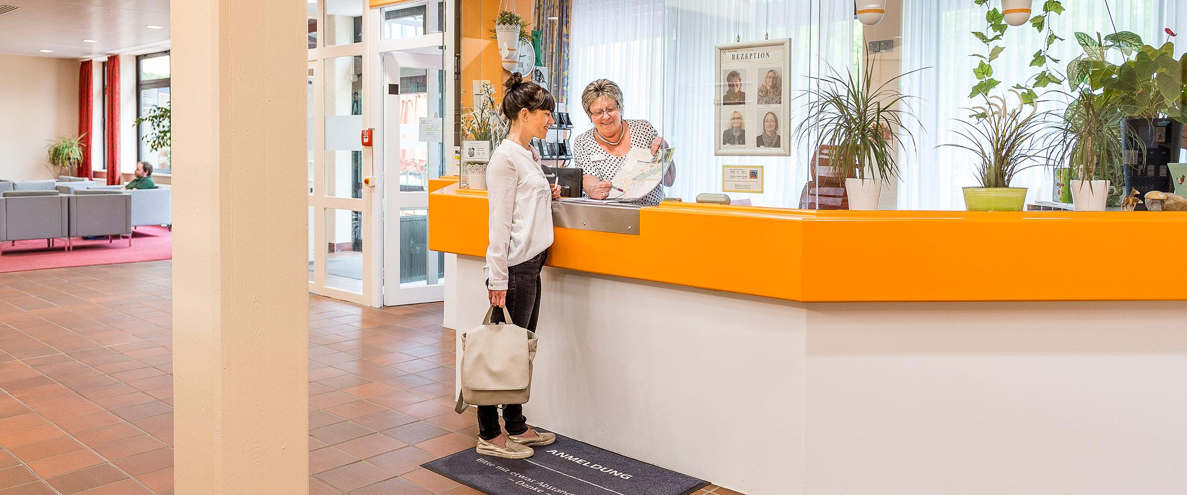 Die Rezeptionistin erklärt einer Patientin etwas an der Rezeption der MEDIAN Klinik für Psychosomatik Bad Dürkheim