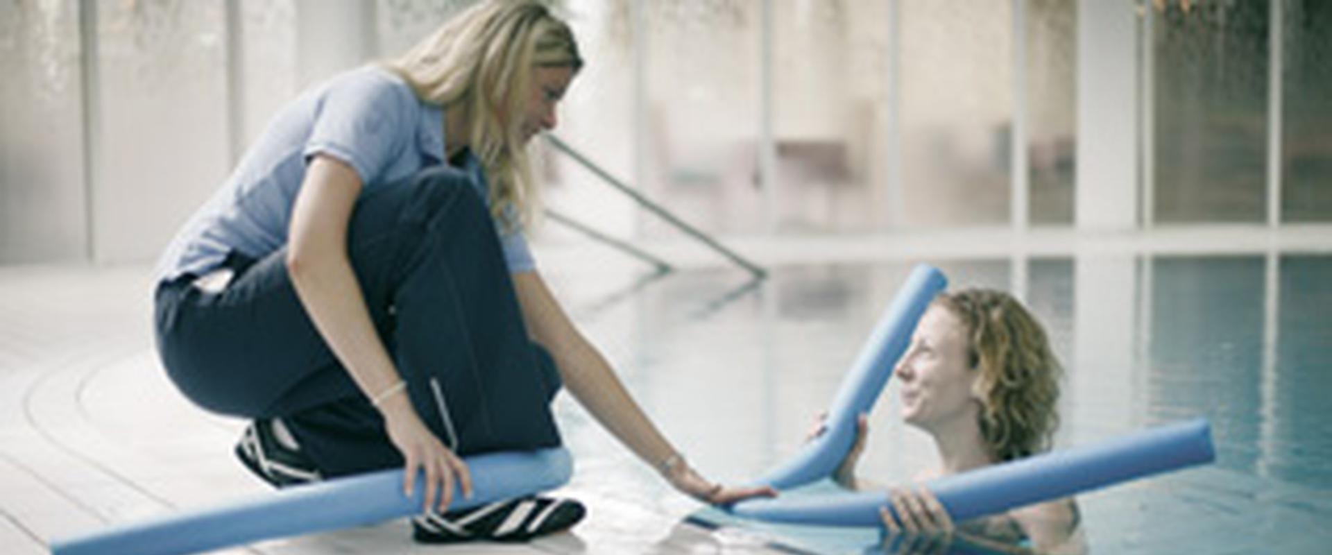 Patientin schwimmt im Schwimmbecken und unterhält sich mit einer Pflegerin in der MEDIAN Frankenpark Klinik Bad Kissingen