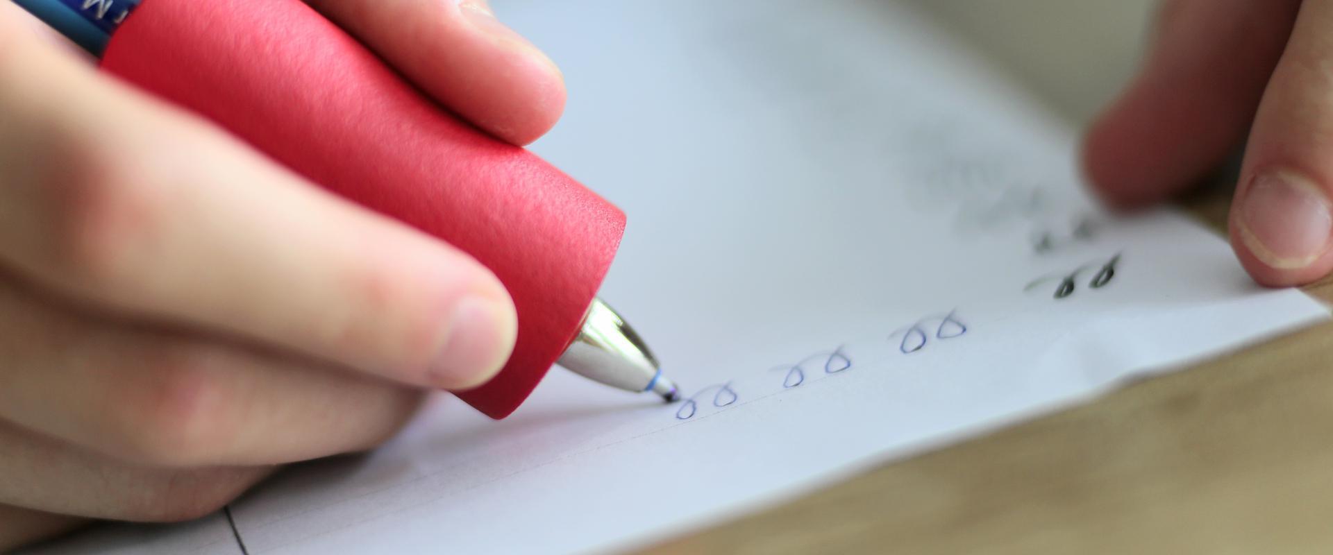 Nahaufnahme einer Hand die etwas auf ein Blatt Papier schreibt in der MEDIAN Kinder- und Jugendklinik Beelitz