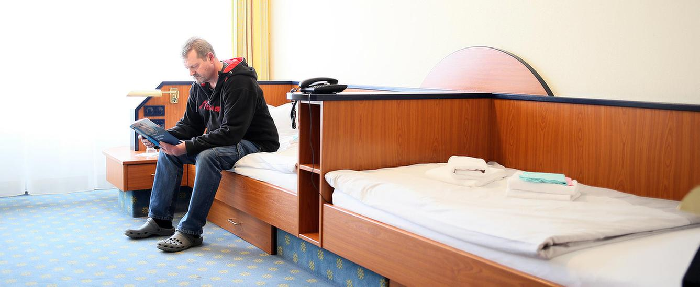 Patient sitzt auf seinem Bett in seinem Zimmer und ließt ein Buch in der MEDIAN Psychotherapeutische Klinik Bad Liebenwerda