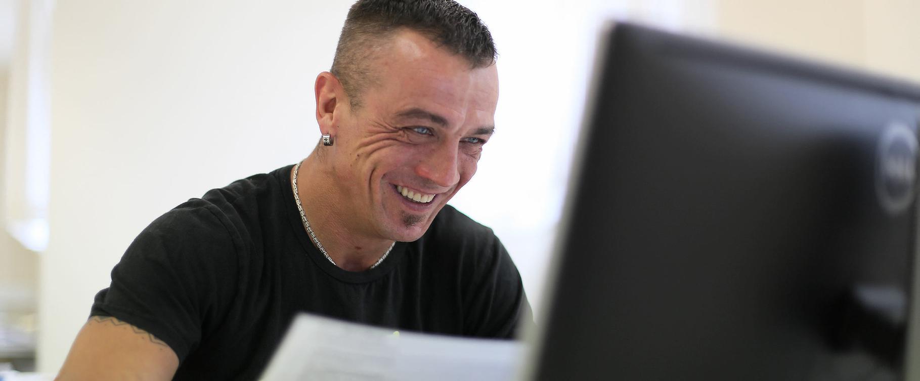 M-Check der MEDIAN Kliniken Mann der in einen laptop schaut und lacht