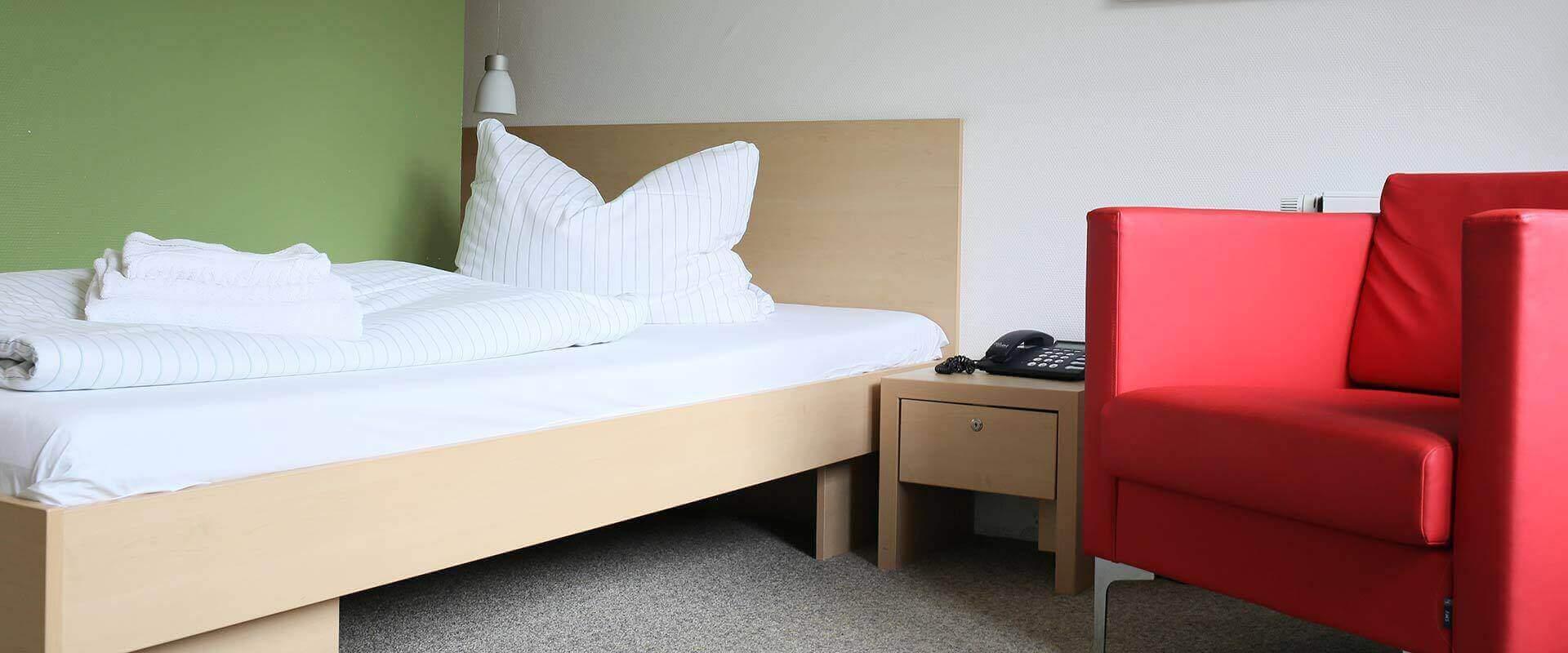 Zimmer mit Bett und Stuhl in dem MEDIAN Zentrum für Verhaltensmedizin Bad Pyrmont – Klinik für Psychosomatik