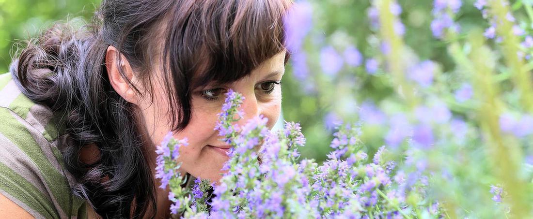 Frau riecht an Blumen im Garten der MEDIAN Klinik Bad Tennstedt