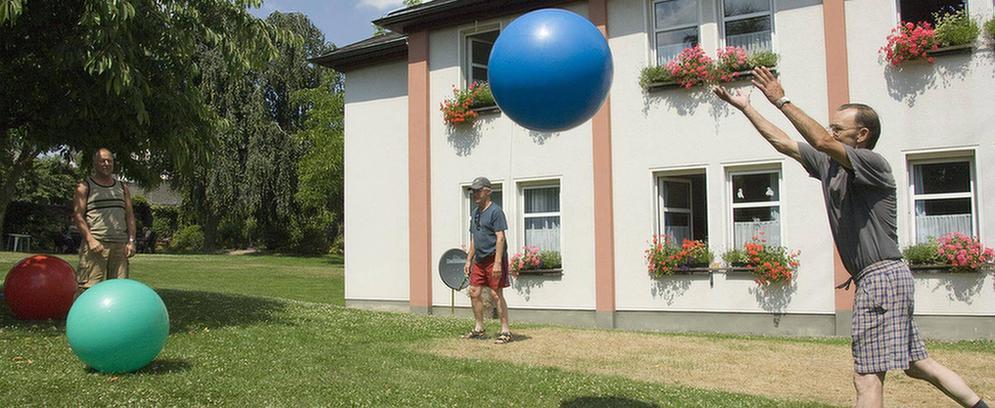 Patienten spielen mit Gymnastikbällen im Garten des MEDIAN Therapiezentrum Bassenheim