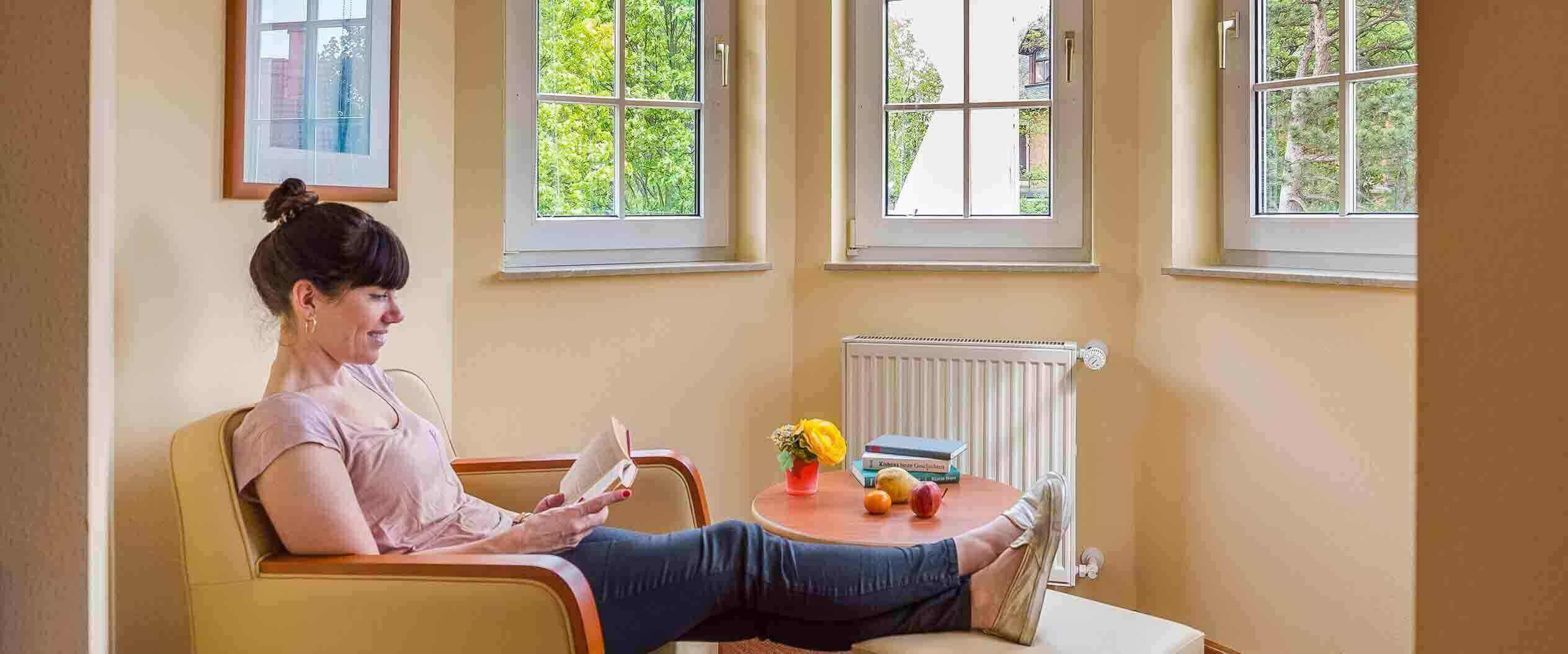 Patientin sitzt in der Leseecke der MEDIAN Privatklinik Berggarten Deidesheim