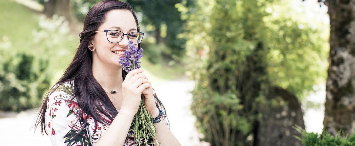 Eine Patientin riecht an Blumen in der MEDIAN Franz-Alexander-Klinik Nordrach