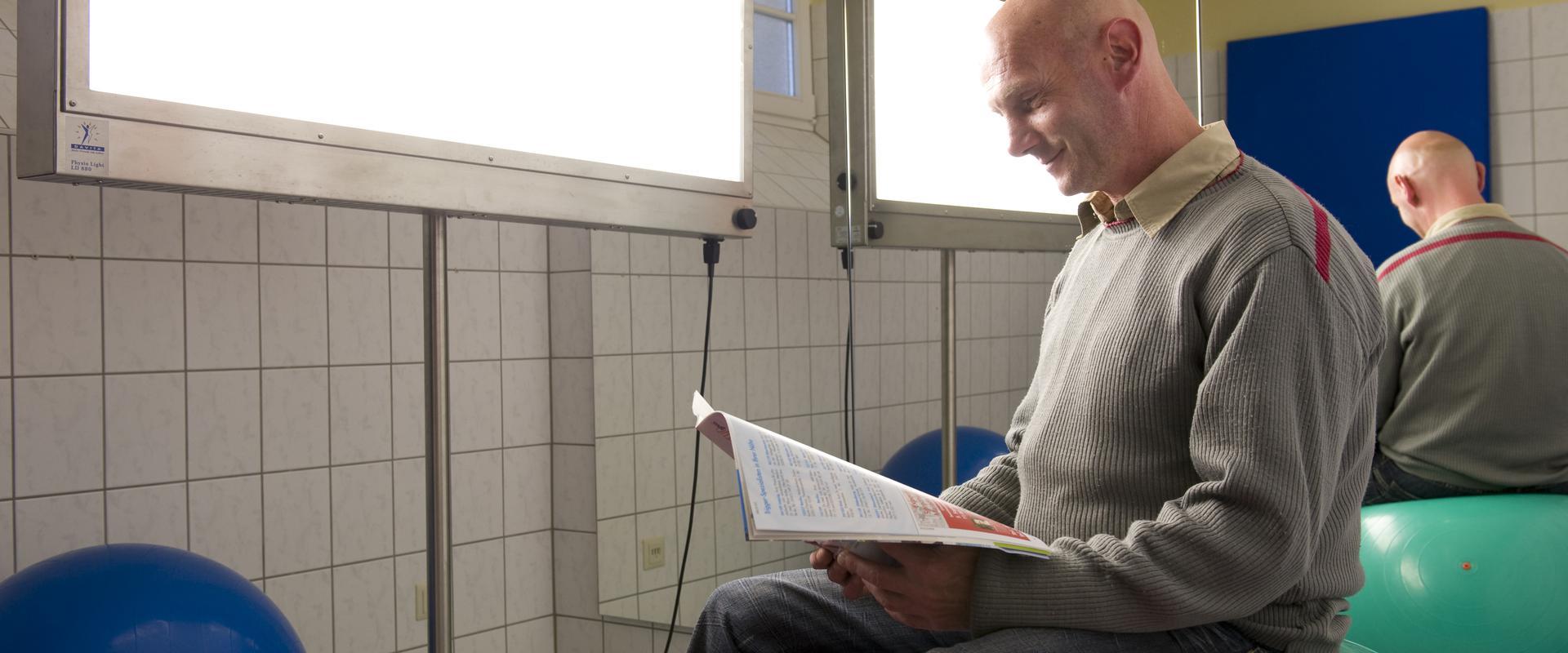 Patient sitzt auf einem Fitnessball und ließt in der MEDIAN Klinik Römhild