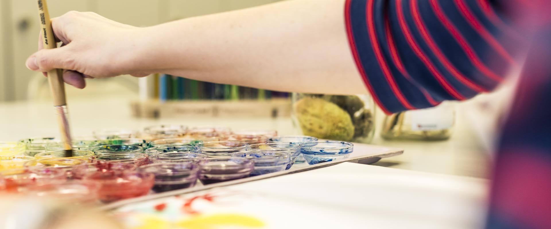 Detailaufnahme Pinsel wird in Farben getaucht in der MEDIAN Klinik Bad Lobenstein