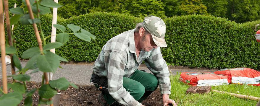 Mann arbeitet im Garten vom MEDIAN Soziotherapeutisches Zentrum Haus Seeblick