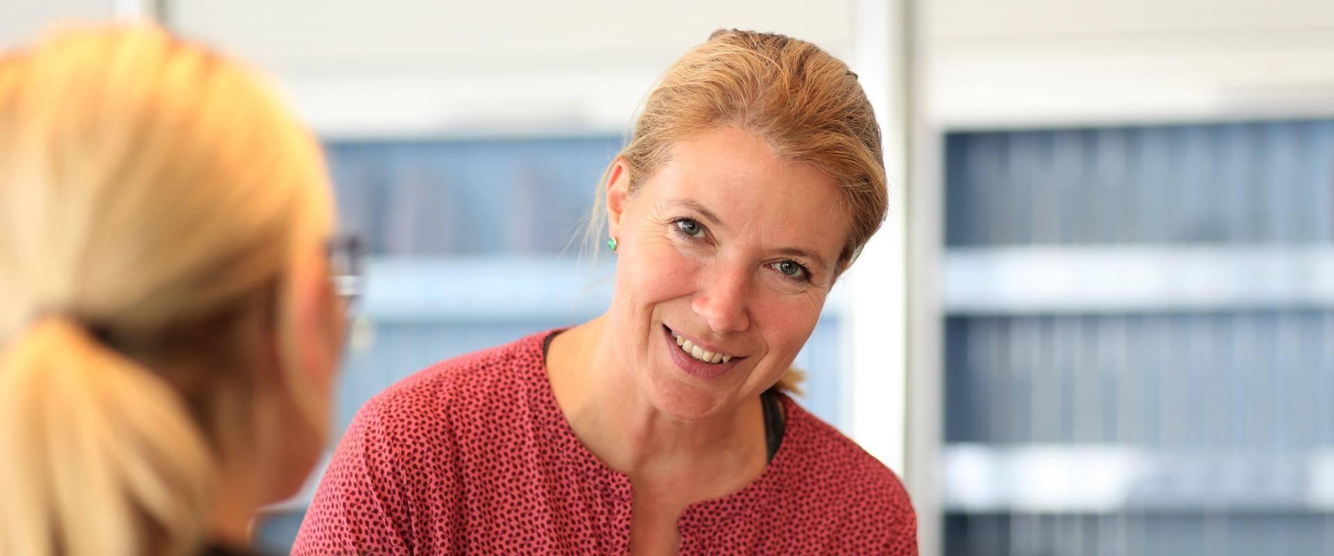 Lächelnde Kundin bei der Anmeldung und Aufnahme im MEDIAN Therapiezentrum Haus Remscheid