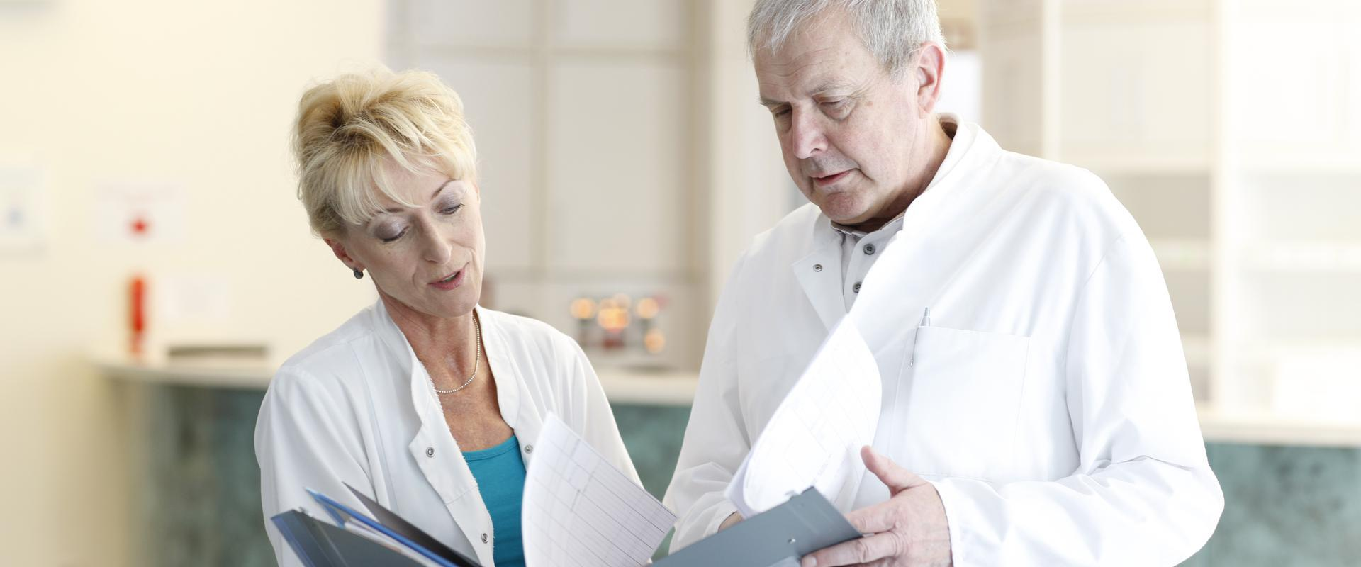Ein Arzt und eine Ärztin studieren gemeinsam wichtige Dokumente in den MEDIAN Gesundheitsdienste Koblenz